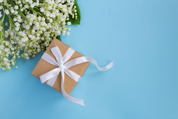 Gift box with white ribbon and lilies of the valley