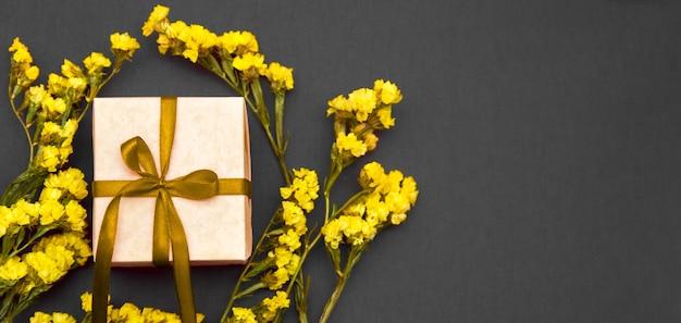 노란 리본과 회색 바탕에 노란색 꽃 선물 상자. 트렌드 색상.