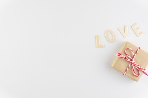 Gift box and word love on white background with space for text, valentine's day