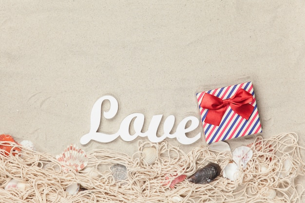 Gift box and word love with net and shells