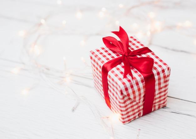 Gift box in wrap near illuminated fairy lights
