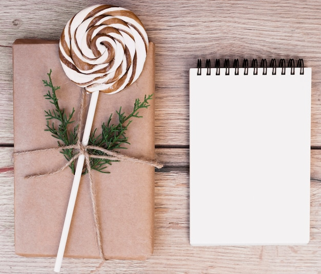 Gift box in wrap with lollipop near notepad