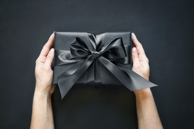 Gift box wrapped in black in female hand on black surface. top view.