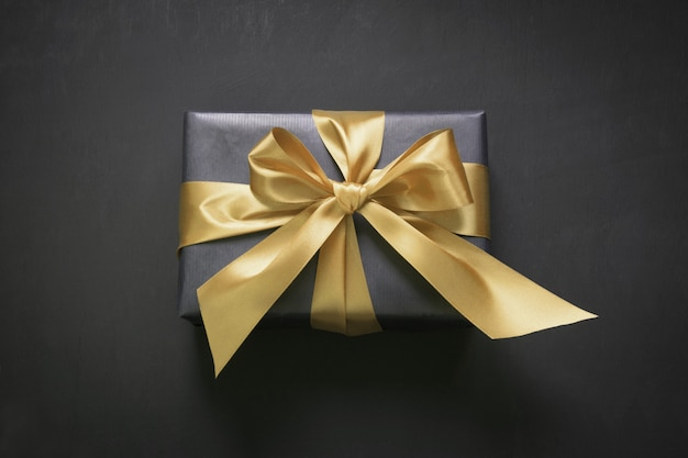 Gift box wrapped in black paper with gold ribbon on black surface.