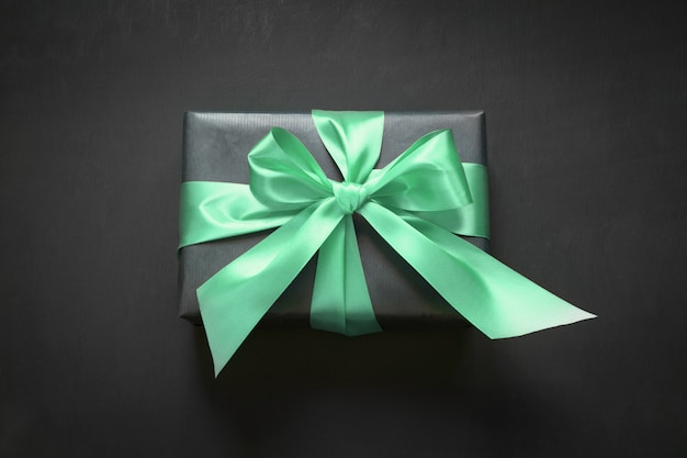 Gift box wrapped in black paper with neo mint ribbon on black surface.