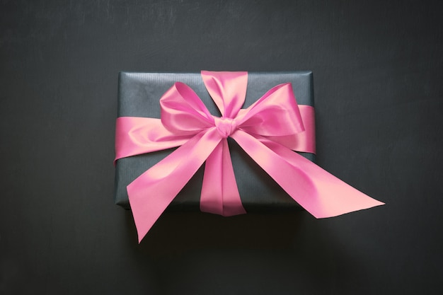 Gift box wrapped in black paper with pink ribbon on black surface
