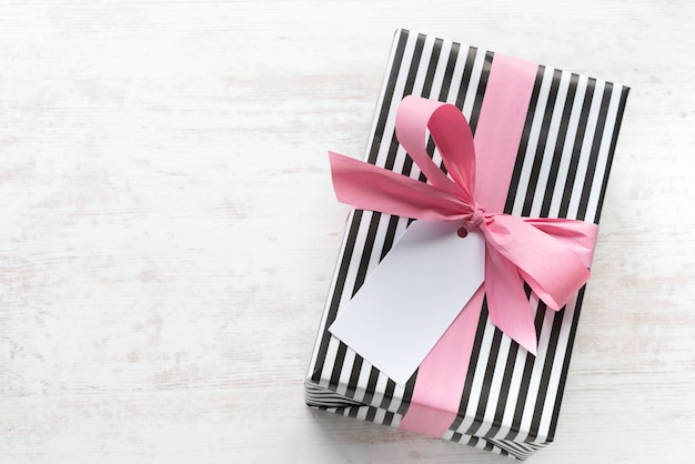 Gift box wrapped in black and white striped paper with pink ribbon on a white wood old background