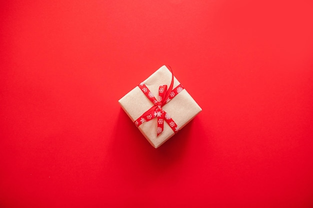 Gift box wrapped in craft paper with red ribbon bow and copyspace on red background