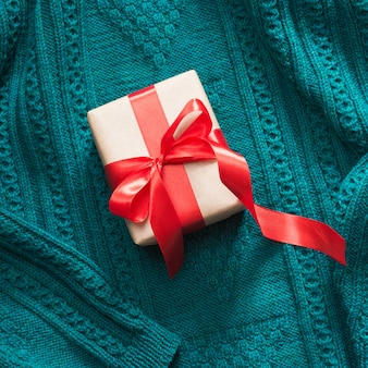 Gift box wrapped in craft paper with red ribbon on knitted surface.