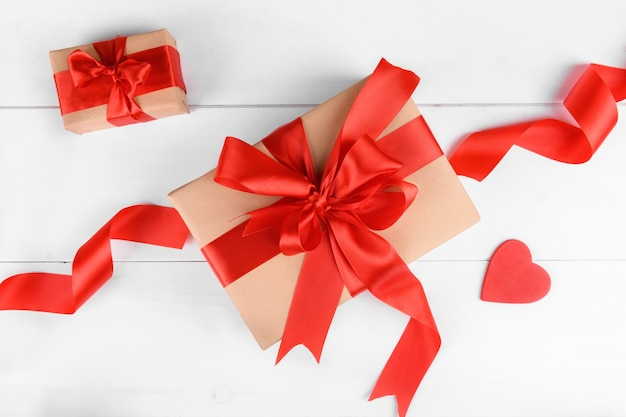 Gift box wrapped in craft recycled paper with red ribbon bow and red heart on a white wooden background.