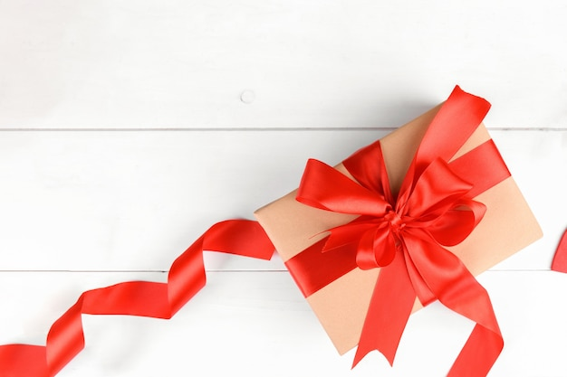 Gift box wrapped in craft recycled paper with red ribbon bow on a white wooden background.