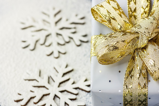 Gift box wrapped in grey silver paper golden ribbon on snow flakes background.