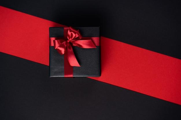 Подарочная коробка в черной бумаге с красной лентой и бантом на черно-красном фоне.