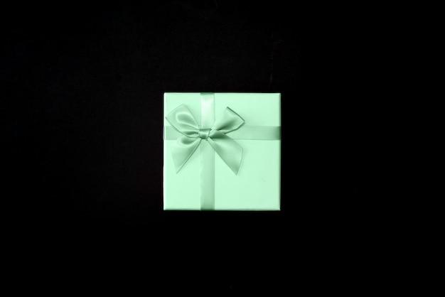 선물 상자 검은 표면에 네오 민트 리본 검은 종이에 싸서. 평면도.