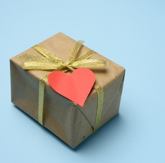 茶色の紙と赤い紙のハートに包まれたギフトボックス