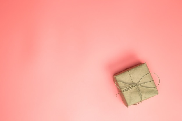 ピンクの背景にピンクの茶色の紙のギフトボックスに包まれたギフトボックス