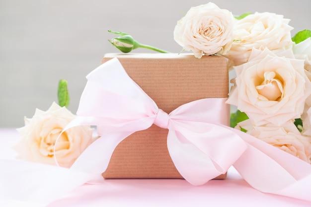 ピンクの背景にピンクのバラと茶色の紙で包まれたギフトボックス。グリーティングカード。