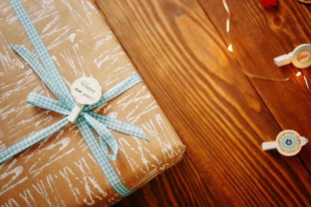 木製のテーブルに青い市松模様のリボンとクラフト紙で包まれたギフトボックス