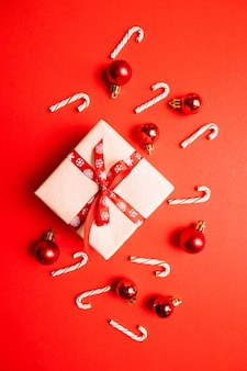 Подарочная коробка, завернутая в крафт-бумагу с красным бантом из ленты, леденцом, елочными шарами на красном фоне. современная креативная минималистичная однотонная праздничная композиция