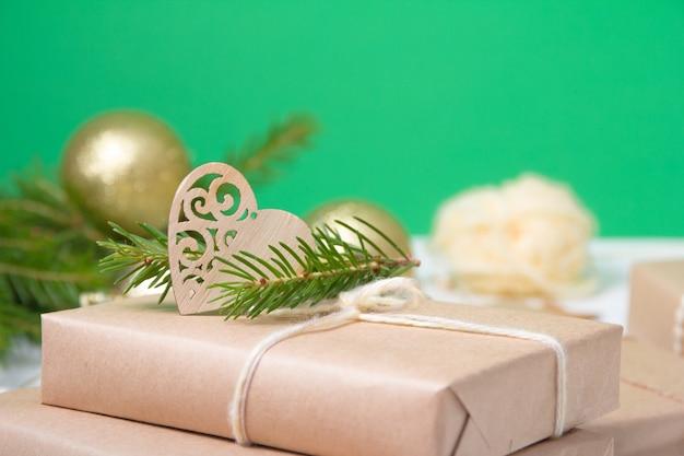 Подарочная коробка, завернутая в крафт-бумагу и украшенная деревянным сердцем и еловой веточкой на желтом фоне, концепция эко-рождества