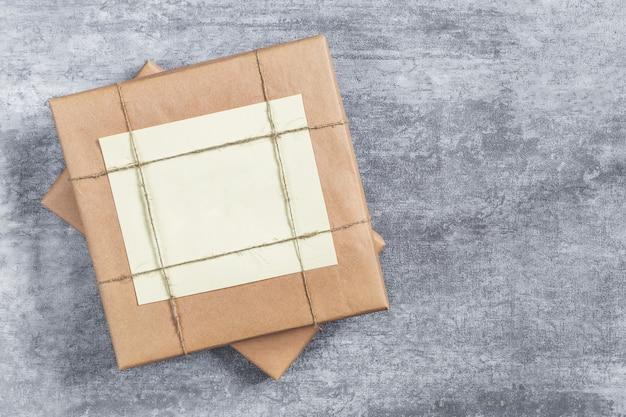 Подарочная коробка, завернутая в крафт-бумагу и перевязанная джутовой нитью на сером фоне.