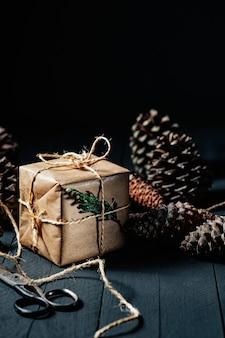 Подарочная коробка, завернутая в крафт-бумагу, канатные ножницы и ананасы на черном деревенском дереве