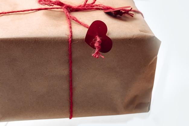Подарочная коробка в крафтовой упаковке, перевязанная веревкой с сердечками. экологичная биоразлагаемая упаковка. подарок в упаковке своими руками.