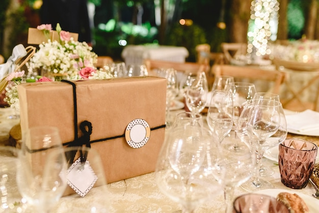 결혼식 피로연의 우아한 테이블에 종이로 싸서 활과 빈 레이블로 무료 텍스트를 포함하는 선물 상자