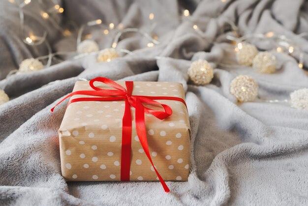 Подарочная коробка, завернутая в бумагу в горошек с красной лентой, с декоративными огнями в качестве фона