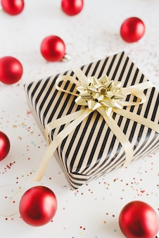 Gift box wrapped in kraft paper with golden ribbon, red christmas balls and star shaped confetti on white background