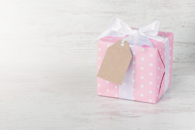 Gift box wrapped in pink dotted paper and tied satin bow over white wood.