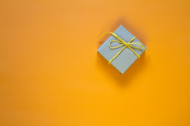 Gift box wrapped in recycled paper tied with yellow twine