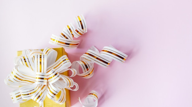 Gift box wrapped in white and gold striped ribbon on pastel pink background. copy space