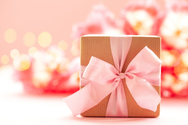 Gift box wrapped with craft paper and pink bow on pink flowers background.