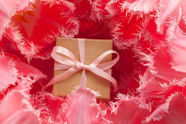 Gift box wrapped with craft paper and pink bow in pink tulip flowers.