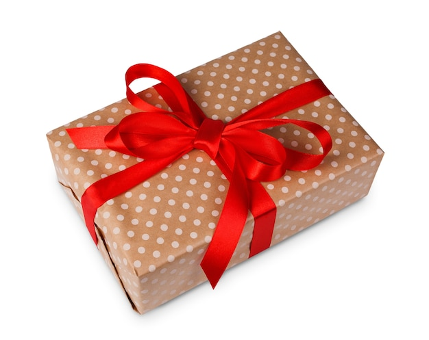 Gift box wrapped with dotted beige paper and red satin ribbon, isolated on white