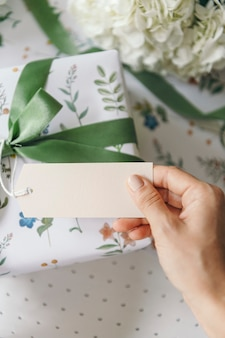 Gift box wrapped with floral patterned paper with a card