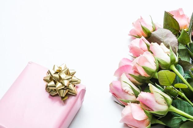 Confezione regalo avvolta con carta rosa con un nastro accanto a un bouquet di bellissime rose rosa