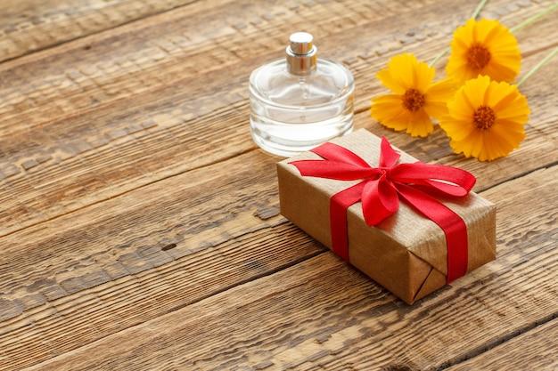 Подарочная коробка, обернутая красной лентой, и флакон духов на деревянных досках с желтыми цветами. вид сверху.