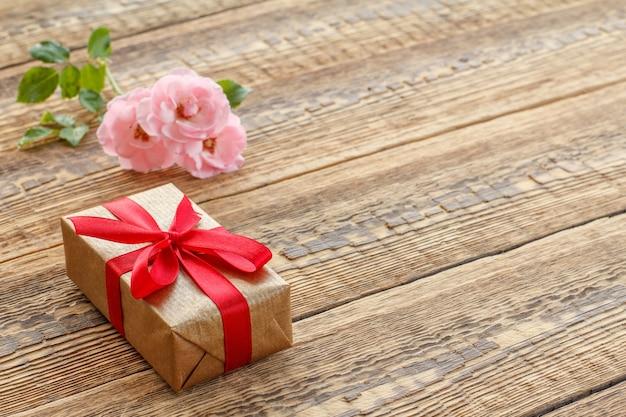 Подарочная коробка, обернутая красной лентой на старых деревянных досках, украшенных розами. вид сверху с копией пространства.