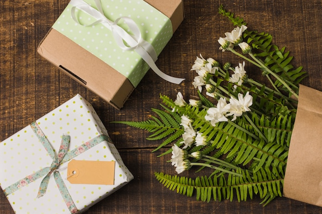 Gift boxed with flowers and leaves in paper bag over wooden table