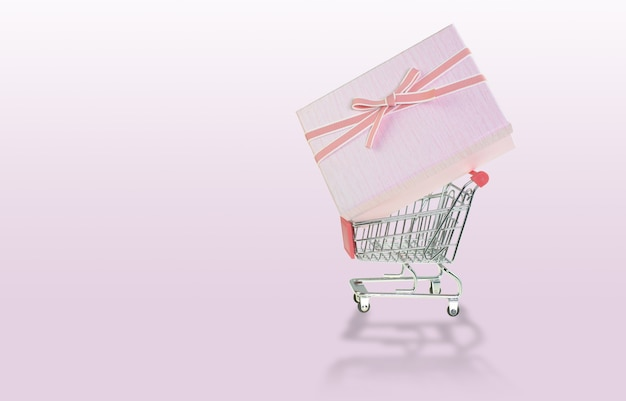 Gift boxes on 4 wheel trolley shopping cart at the pink background