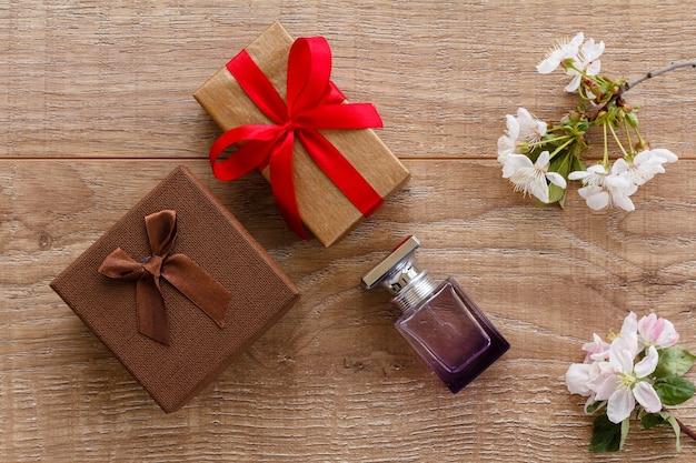선물 상자, 나무 배경에 벚꽃과 사과 나무의 꽃 가지가 있는 향수 한 병. 평면도. 휴일에 선물을 주는 개념.