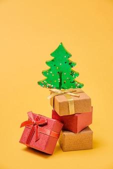 コピースペースのある黄色の背景にギフトボックスとクリスマスツリー。