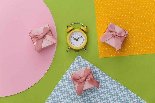 創造的なカラフルな紙の背景にギフトボックスと目覚まし時計。ミニマリズム