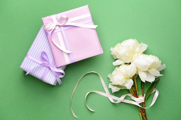 Подарочные коробки и красивые цветы на цветном фоне