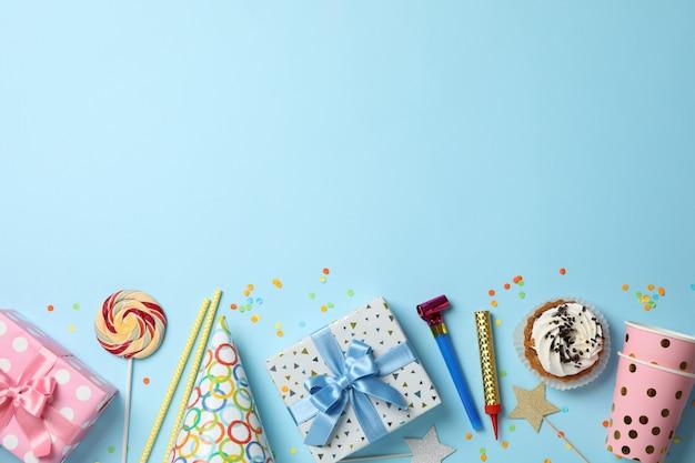 Подарочные коробки и аксессуары на день рождения на синем фоне, вид сверху