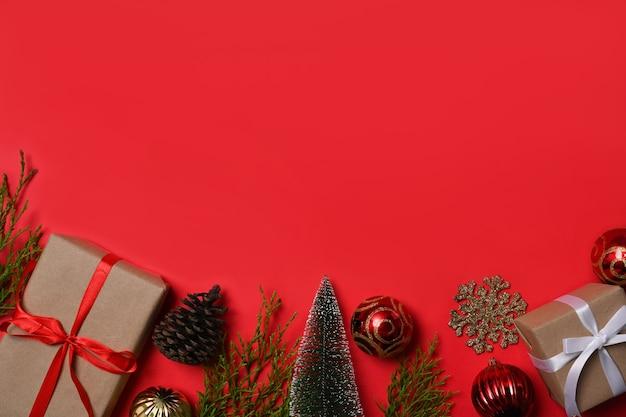 コピースペースと赤い背景の上のギフトボックスとクリスマスの飾り。