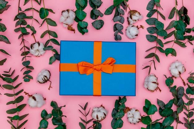 Подарочные коробки и хлопок с ветвями эвкалипта на розовом фоне. тема здравоохранения