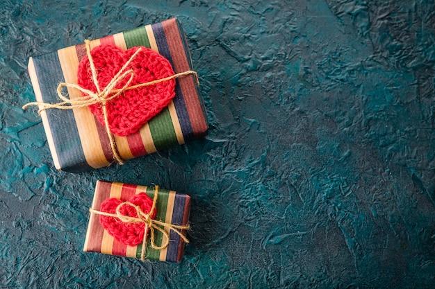 暗い背景にギフトボックスとかぎ針編みのバレンタインハート。
